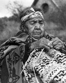 Agnes George, nee Johnny; knitting a Cowichan pattern; the Butter Church on Comiaken Hill behind;...