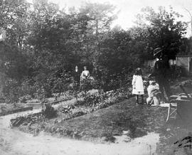 Four people and dog in the garden at Point Ellice; A.D. Crease Collection, Box 1.