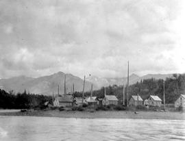 Homes seen from the river with mountains in the background.