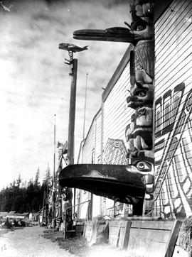 View of Alert Bay, BC, showing totem poles and house-fronts.