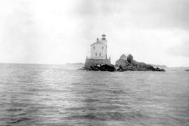 A large lighthouse on a small rock.