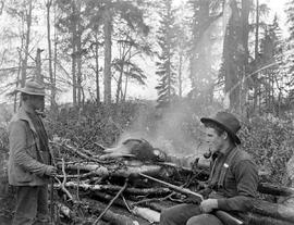 Patrick Sharkey, camp cook during the Fraser Lake survey, cremates a dead dog which he shot after...