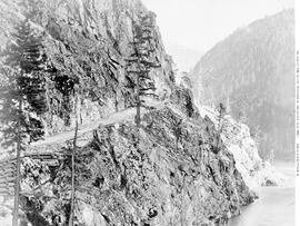 Notice the steep descent of the road from the middle of the photo.  On one occasion the break [sic] of Barnards stage coach broke and Jim Newland saved the situation.  A view on the Fraser River wagon road at the 19 Mile post.