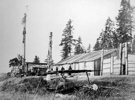 Indian monumental carvings and totems with dressed figures in front of the Chiefs lodges at Comox