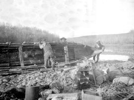 Surveyors repairing a boat on the lower Nechako River.