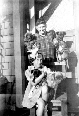 Emily Carr with neighbour Phyllis Hudson, four dogs and her monkey, Woo.