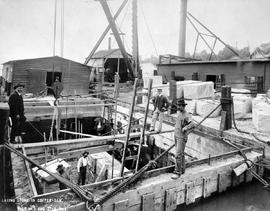 """Laying stone in the coffer dam""; construction of the Fraser River Bridge in New Westmi..."