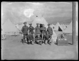 Soldiers pose outside their tent
