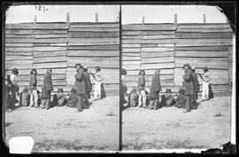 Group of natives standing in front of wall; from the Newcombe collection, box 7.16.
