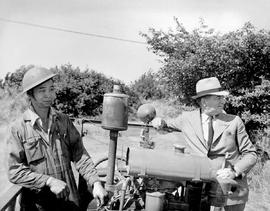 Honourable Ian Mackenzie, with Harry Hing, inspecting Richmond A.R.P. fire fighting equipment