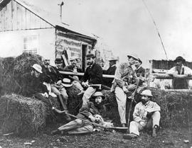 A group of colonial officials at rest, during hunting trip to Grouse Creek; Governor Frederick Seymour sitting on hay bail in centre, Matthew Baillie Begbie, hatless, at left with do