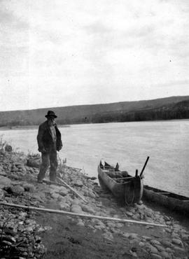 Gavin Hamilton and his canoe on the banks of the Peace River.