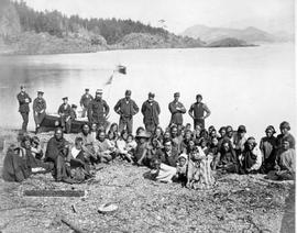 """Nootka Sound Indians, Vancouver Island, Where Captain Cook was in March 1778""; Friendly Cove; also in photo is Dr. I.W. Powell, Indian Commissioner; boat and seamen"
