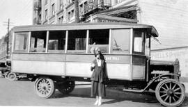 A woman posed beside the Lake Hill bus at the Campbell Building, completed in 1912, at the southe...