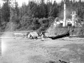 Department of Mines camp in front of an abandoned long-house and totem poles at Tanoo