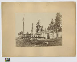Indian Village Comox Vancouver Island.  The highest carving has a carved wooden head suspended by...