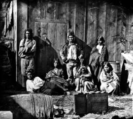 Indians at Lytton B.C.  Indian group at Lytton where the Thompson River joins the Fraser River.  Indian Chief in Buckskin coat and fur hat also Indian woman nourishing her child in a basket cradle.  These indians [sic] ride on horseback and differ very much from the Vancouver Island Indians who do not possess horses.