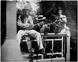 Four men, two aiming rifles from the porch of a building