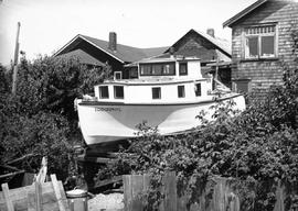 "Handmade gas boat ""Edidonphyl"" in the backyard of the the Munday house, Tempe Crescent, North Vancouver; box 34 ""1936 Klini Kline, Silversthrone""."