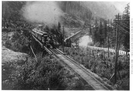 View From Top Of A Snowshed On Canadian Pacific Railway Mainline In Rogers Pass Near Laurie.  3/4 Right Of Locomotive And String Of Open-Platform Coaches Heading Toward Camera O