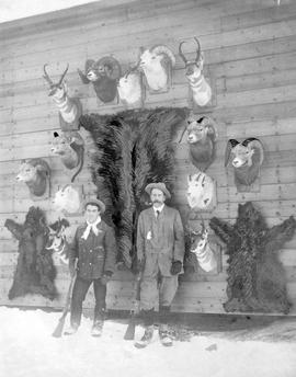 J. K. Brewster and friend with hunting trophies in Banff; photo embellished