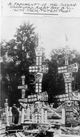 """A fragment of the Indian graveyard, Alert Bay, BC, with their totem poles."""