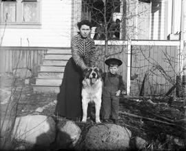 Mrs. French in the garden with a small boy and a large dog.