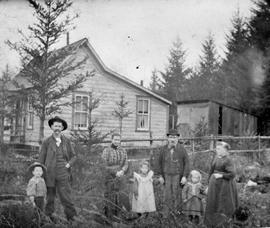 Mr. and Mrs. Gus Cox and family outside their home.