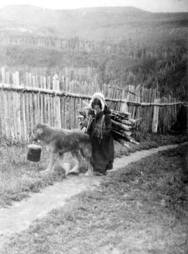 A little Indian girl with a load of firewood on her back; her dog accompanies her; Bella Bella.