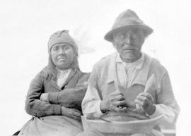 Huu-ay-aht elders Sa'sawatin and his wife Yima'uk; he is holding a small carved canoe i...