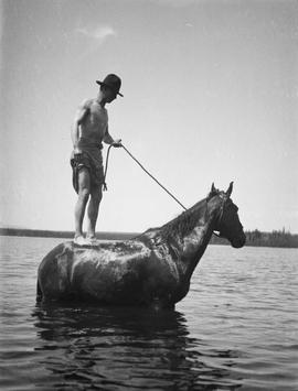 Leonard Butler swimming from horseback on a Sunday at Nahlousa Lake.
