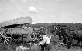 Survey team taking a meal break while carrying a canoe on a freight wagon on the Ootsa-Cheslatta ...