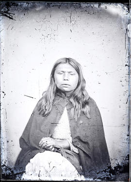 Studio portrait (mid-length) featuring an unidentified Indigenous individual taken at a photographic studio attributed to Frederick Dally.