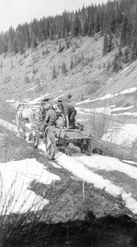 A British Columbia policeman driving along Williams Creek with the body of a lone prospector acci...
