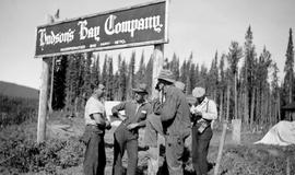 Group at Fort Ware standing under Hudson's Bay Company sign.