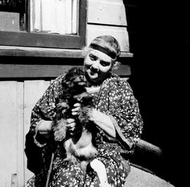 Artist Emily Carr seated on the verandah of her St. Andrew's Street home and holding one of her dogs.
