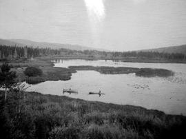 Small rowboat and canoe on Divide Lake in the Highland Valley.