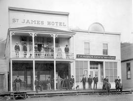Group in New Denver; standing outside the St. James Hotel and T.H. Hoben, General Merchant.