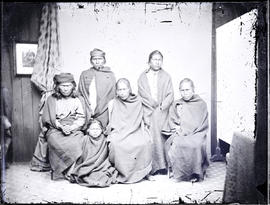Studio portrait featuring of a group of six unidentified Indigenous individuals seated and standing taken at a photographic studio attributed to Frederick Dally.