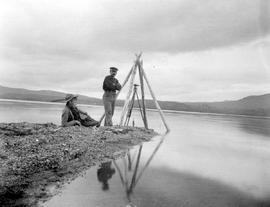 Two surveyors at a triangulation point on the shore of Fraser Lake.