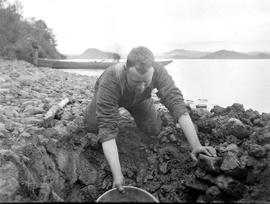 Charlie Heymer digging a well along the shore of Fraser Lake.