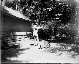 Man outside a cabin aiming a rifle, and a dog