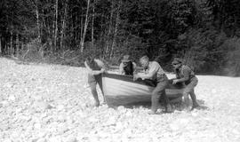 Survey crew portaging a boat along the banks of the Kitlope River.