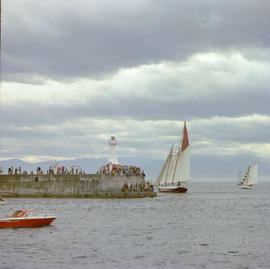 Boats participating in the Victoria Classic Boat Festival rounding the breakwater