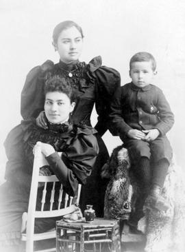 Annie Hunt, standing, with her her sister Jane and brother George, both seated.