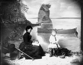 Hannah Maynard and a small girl with her wagon; painted backdrop is Siwash Rock.