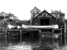 J.J. Robinson, shipwright and boatbuilder; building with sign and boats on waterfront.