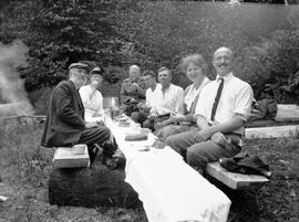 A happy group of picnickers with an excellent picnic table and benched made of slabs of timber.