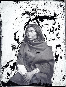 Studio portrait (mid-length) of an unidentified Indigenous individual seated and taken at a photographic studio attributed to Frederick Dally.