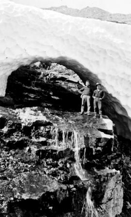 Swannell Survey; two men standing under an icebridge.